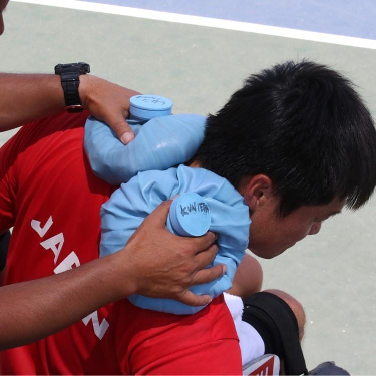 שחקן יפני עם שקיות קירור על הכתפיים