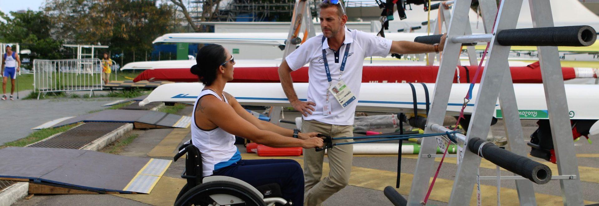 ספורטאית על כסא גלגלים והמנהל עומדים ליד הסולם.