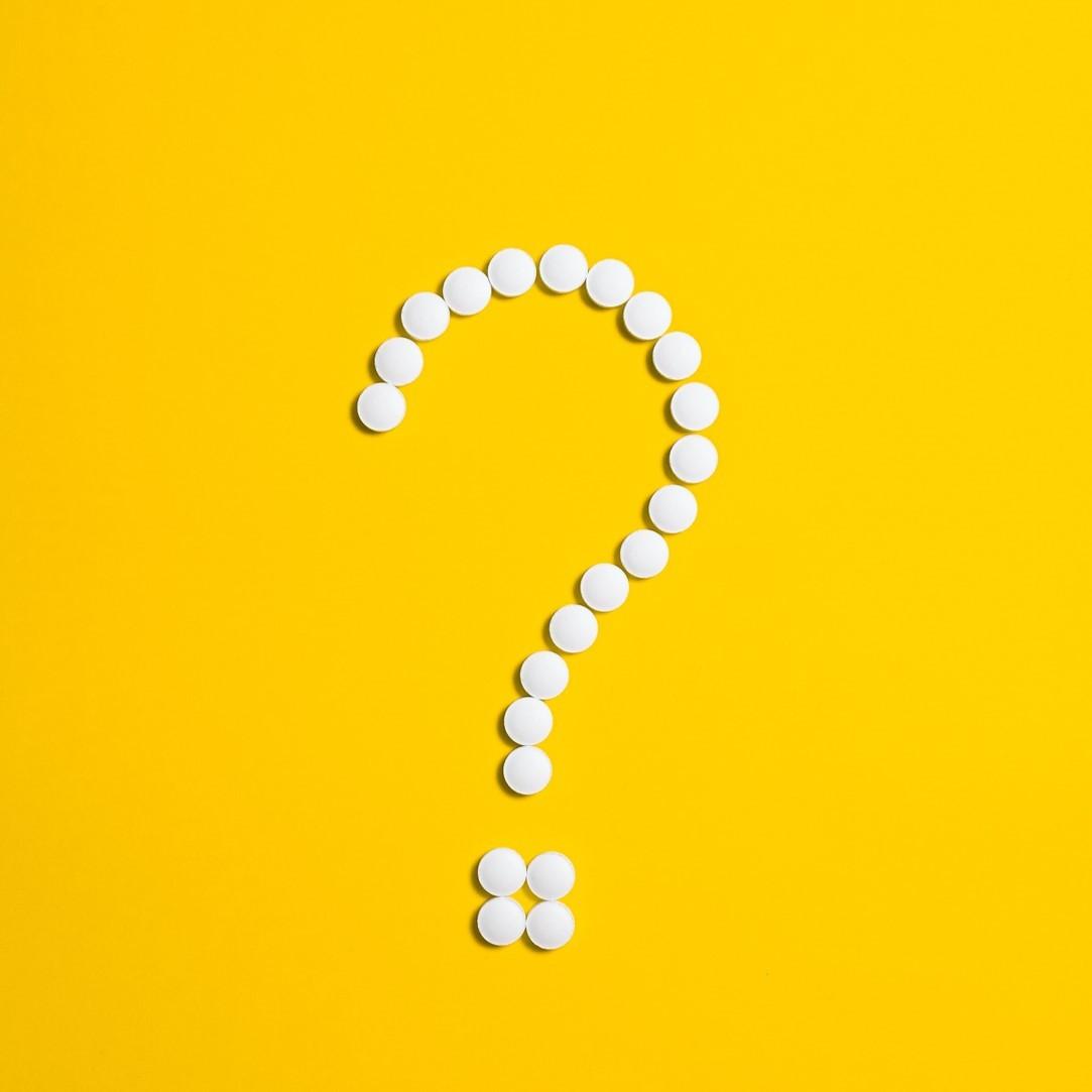 כדורי תרופות לבנים שיוצרים סימן שאלה עם רקע צהוב