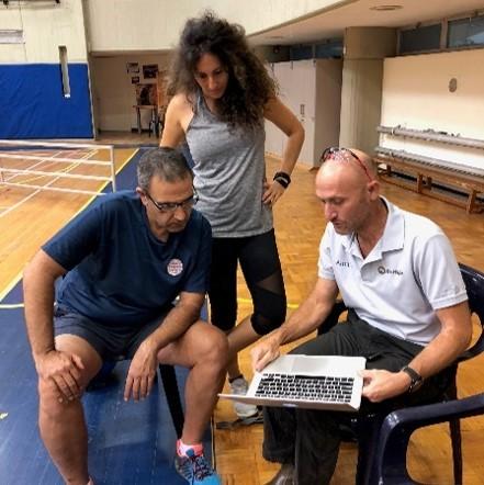 שני אנשים יושבים ומסתכלים במחשב ואשה נוספת עומדת ומביטה גם היא במחשב