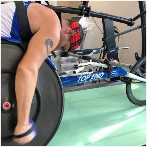 ספורטאי אופני מירוץ לידיים מזיז את הגלגל תוך שהוא נוסע על מסילת בדיקה