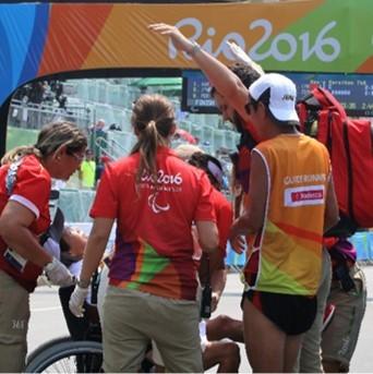 אדם מטיל צל על אדם אחר בכיסא גלגלים, מאחור הכיתוב ריו 2016