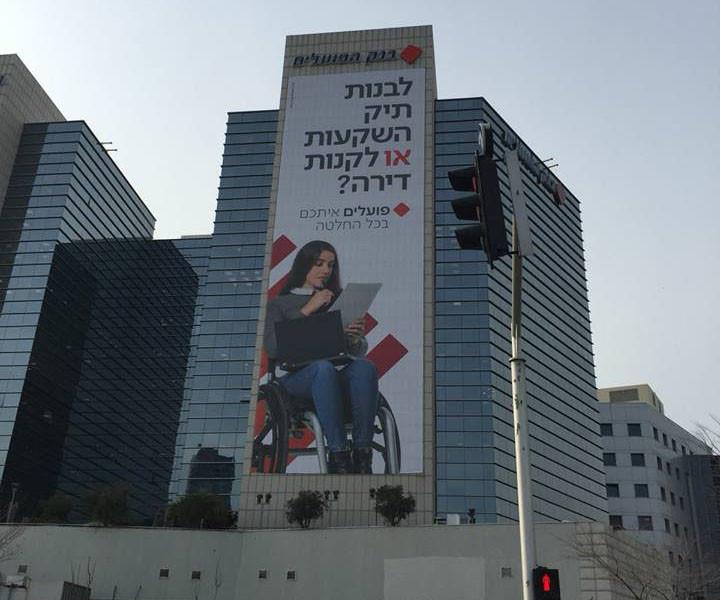 שלט חוצות של בנק הפועלים ששם מופיעה בחורה בכסא גלגלים.