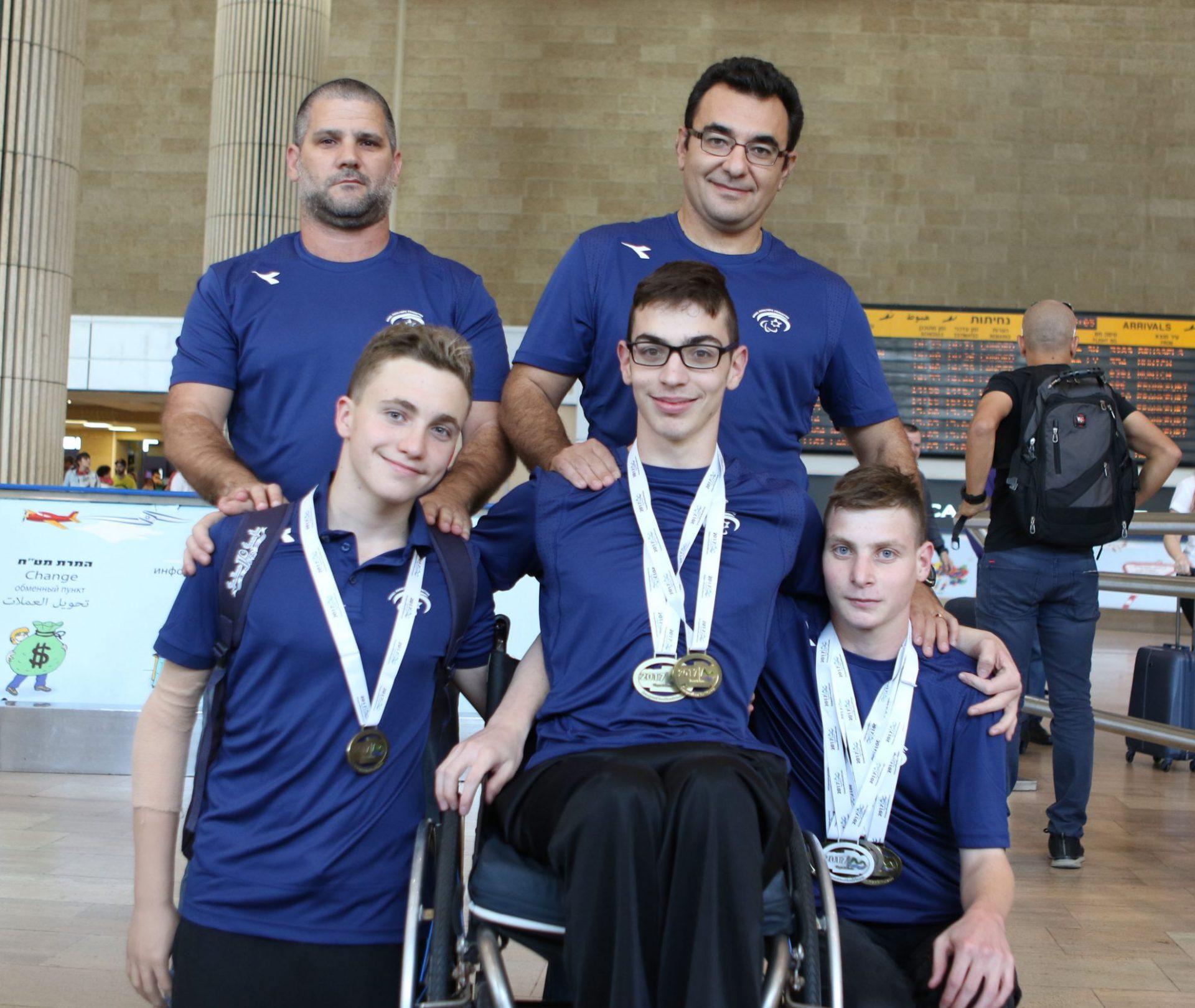 חמישה אנשים מתוכם אחד על כיסא גלגלים ושלושה עם מדליות על רקע שדה תעופה