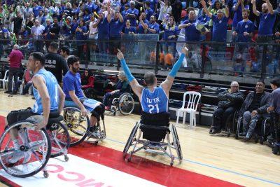 ספורטאי על כיסא גלגלים בגבו למצלמה מניף את ידיו לאות ניצחון מול קהל מריע