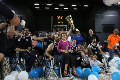 ספורטאי בכסא גלגלים אוחז גביע מונף למעלה, עליו יושבת ביתו ומאחורה ספורטאים נוספים